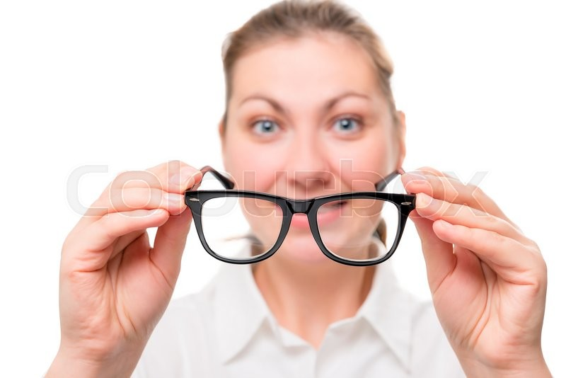 Stock image of 'Woman with poor eyesight wears glasses, focus on glasses'