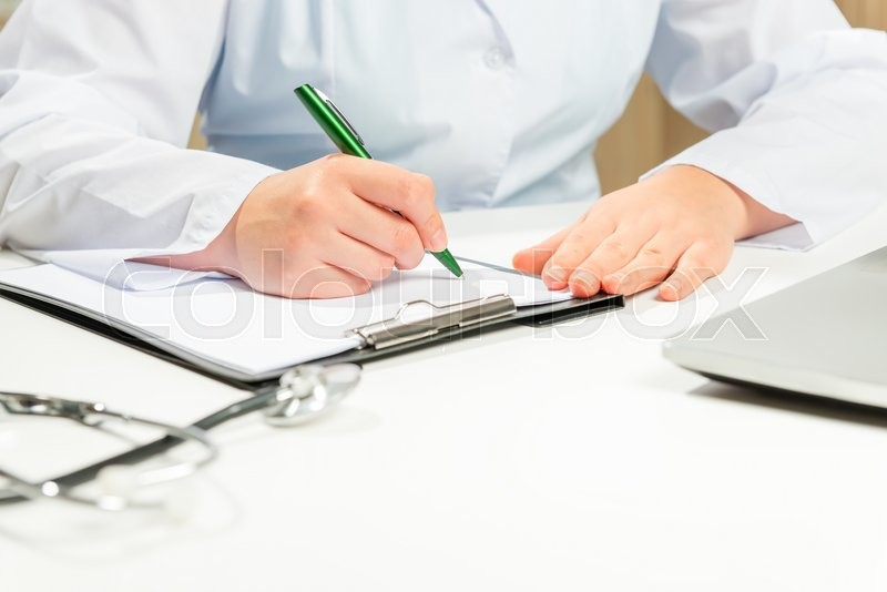 Stock image of 'Hands close-up doctor writes diagnosis in dealing'