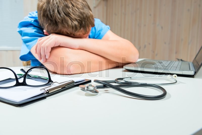 Stock image of 'Tired Doctor sleeps at the table in working hours in the office'