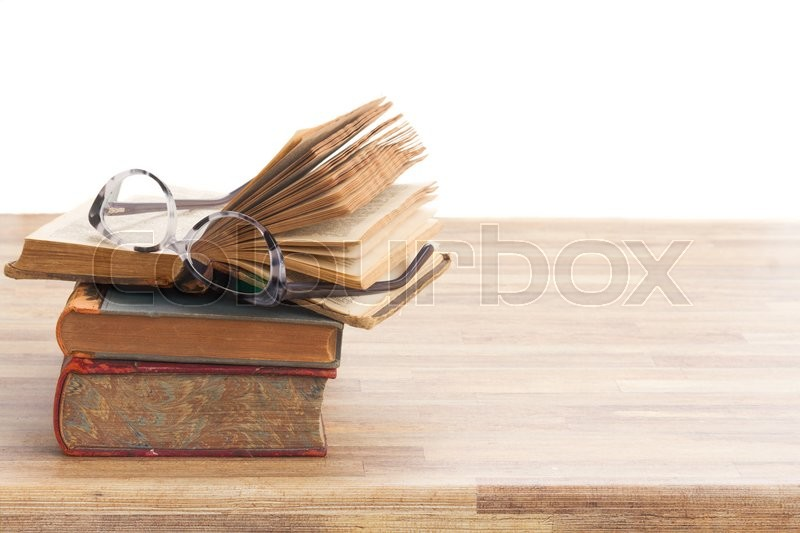 Stock image of 'Stack of Books and glasses on wooden table desktop border isolated on white background'