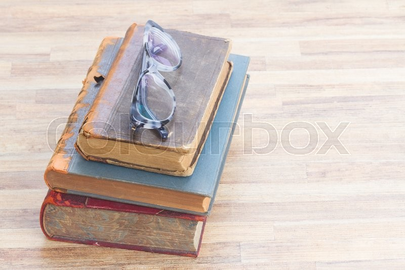 Stock image of 'Books stack and glasses, copy space  on wooden table desktop'