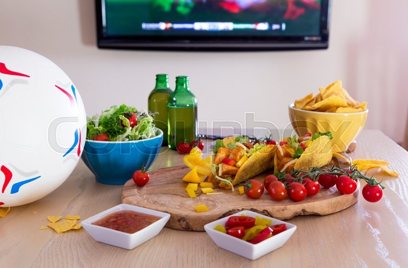 Stock image of 'Mexican tacos and beer on a table with a football. There is a television in the background with sports showing.'
