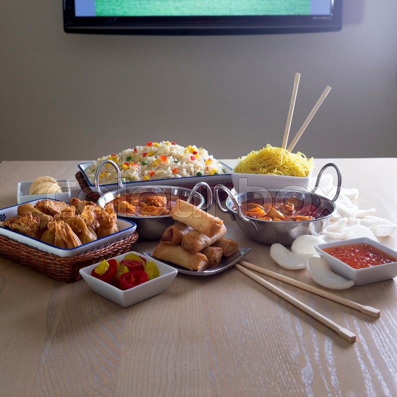 Stock image of 'Selection of chinese and indian food presented infront of a television in a house.'