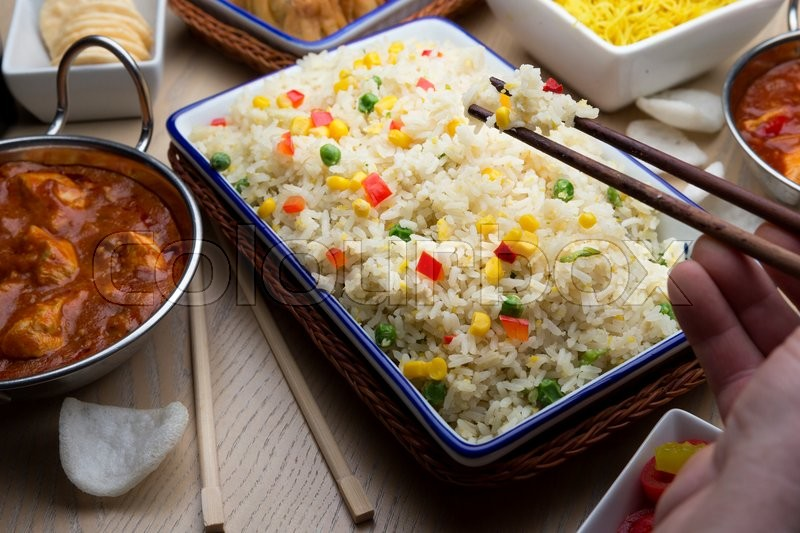 Stock image of 'Close up of a large tray of rice surrounded by chinese food. Someone is taking some rice using chopsticks'