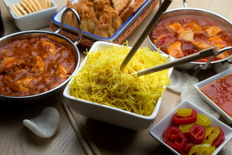 Stock image of 'Close up of a bowl of noodles surrounded by Chinese food'