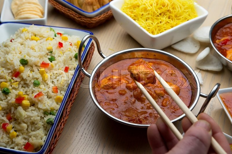 Stock image of 'Close up of chinese food on a table. Someone is taking some curry using chopsticks.'