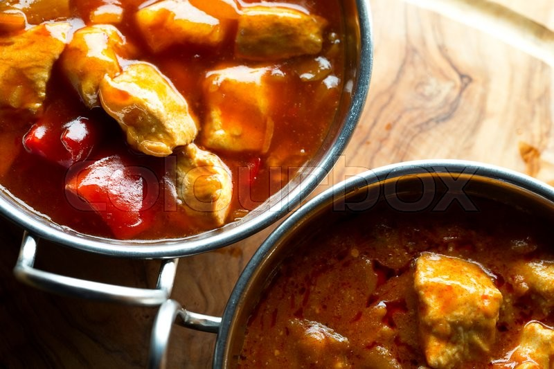 Stock image of 'Close up, view from above of curry in balti dishes on a wooden slab.'
