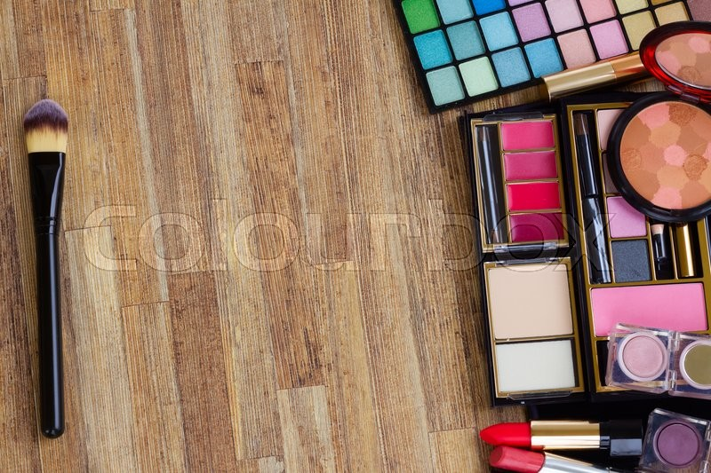 Stock image of 'Frame of  brushes, lipsticks, maskara, eye shadows and  powder on wooden table, top view '