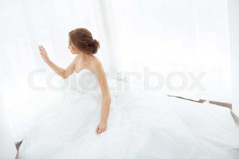 Stock image of 'Beautiful young bride in white wedding dress indoors.  Luxuty model sitting against big window at home. Girl waiting her groom in bright room. Beautiful wedding hairdress. High key photo.'