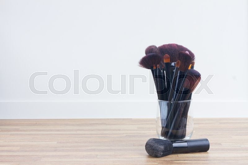 Stock image of 'set of  black make up brushes in glass can on wooden table'