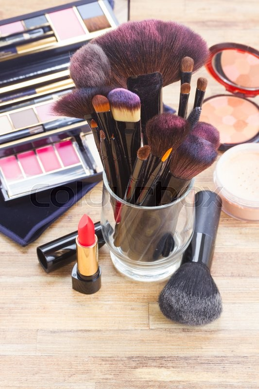 Stock image of 'glass with  brushes and make up products on wooden table'