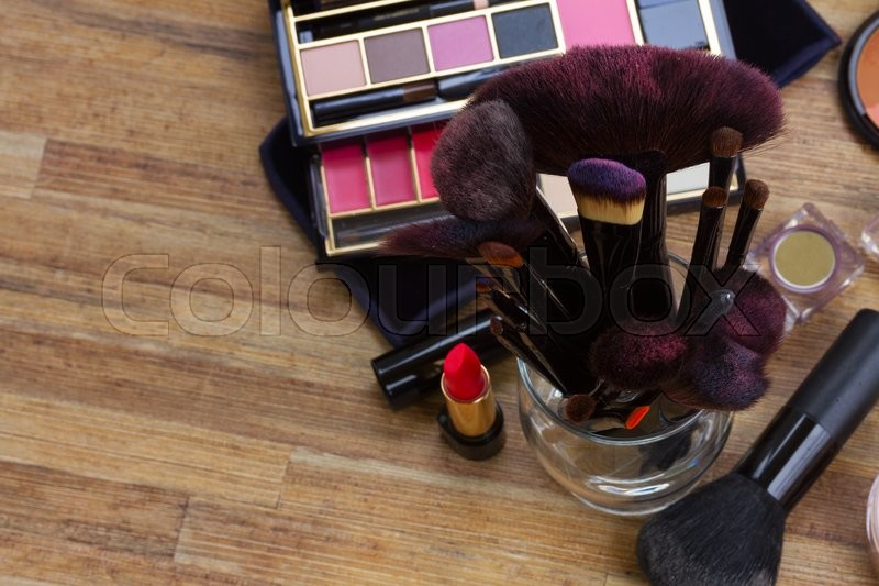 Stock image of 'glass can with  brushes and make up products on wooden table with copy space'