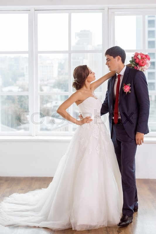 Stock image of 'Wedding couple in love. Beautiful bride in white dress with brides bouquet and handsome groom in blue suit standing and embracing each other indoors in decorated studio room, white bright interior with big window. '