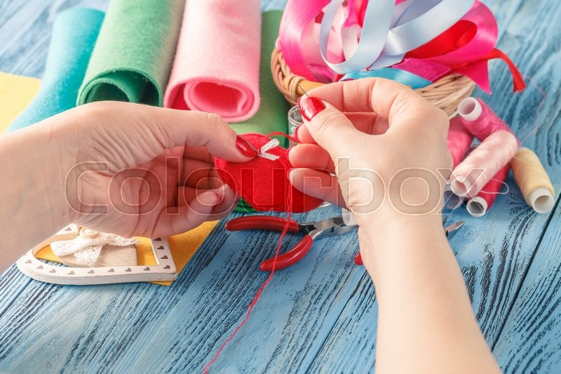 Stock image of 'Female hand with needlework objects on blue wood table'