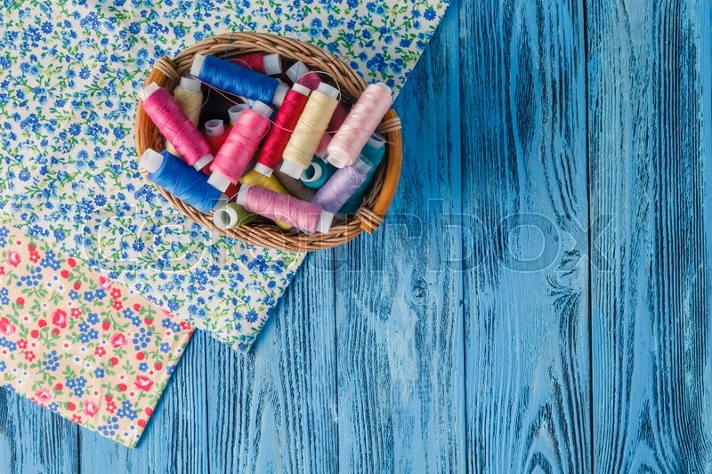 Stock image of 'Colored sewing threads on a old work table'