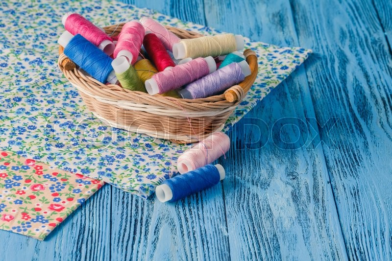 Stock image of 'Multicolor sewing threads on wooden background'