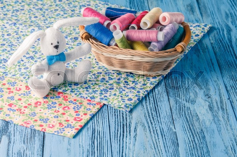 Stock image of 'threads in basket and soft toy on blue table'