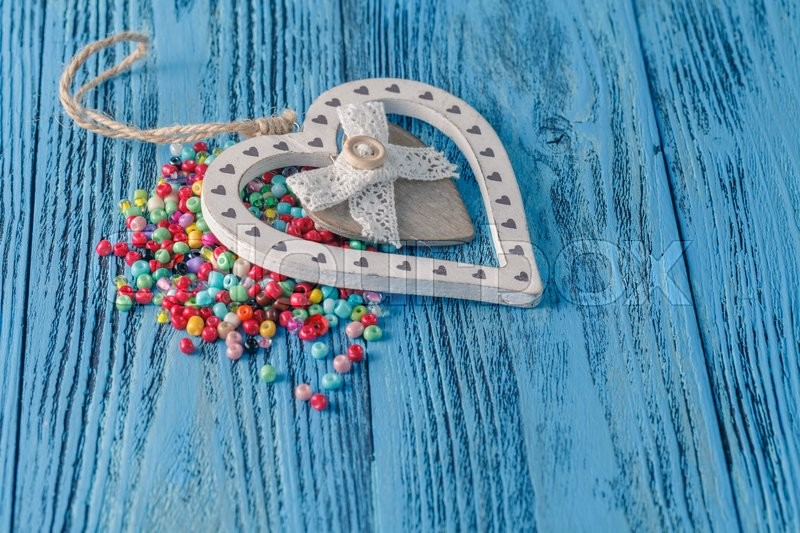 Stock image of 'Different colorful beads on the wooden table'
