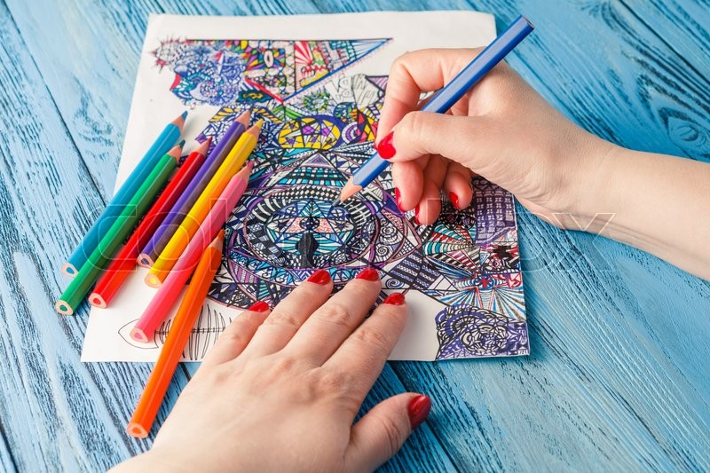 Stock image of 'Adult coloring books colored pencils anti-stress tendency. Hobbies woman's hands painting stress relief painter'