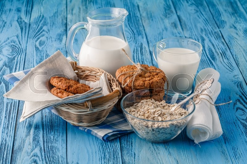 Stock image of 'Oat cookies and milk on blue wooden table'