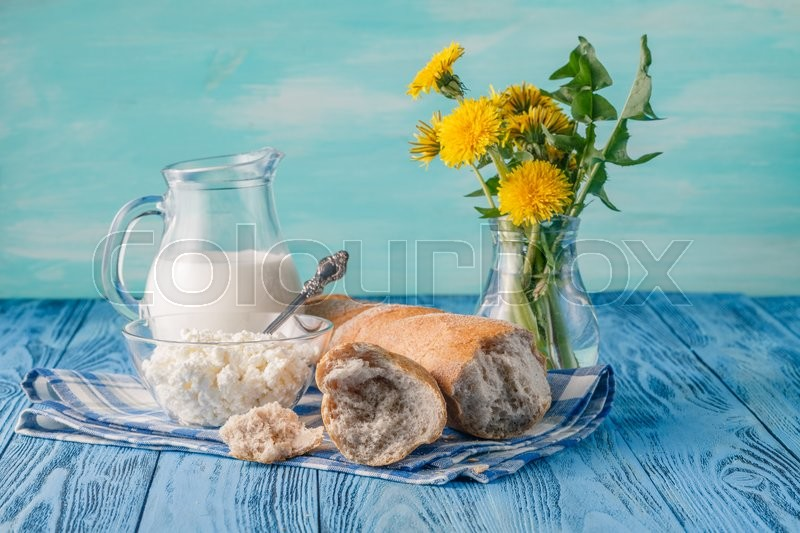 Stock image of 'organic healthy food, cottage cheese and bread. Dandelion flowers on table'