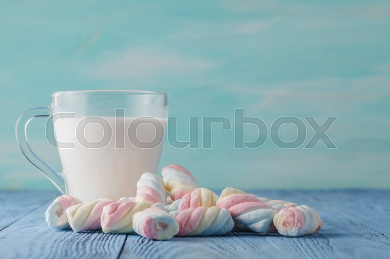 Stock image of 'Milk and twisted marshmallow on bright blue table'