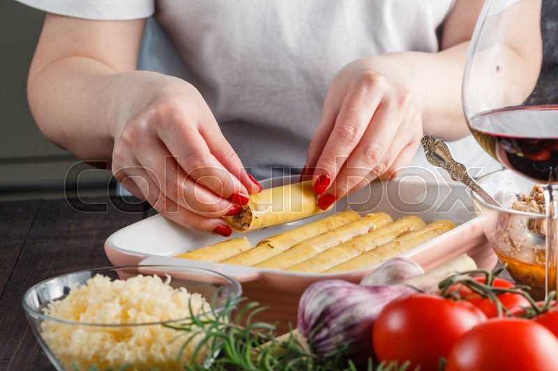 Stock image of 'Woman making cannelloni or lasagne on kitchen'