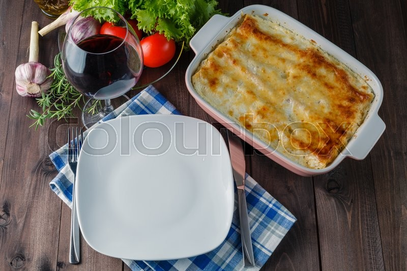 Stock image of 'Fresh prepared lasagne with ingredients on table'