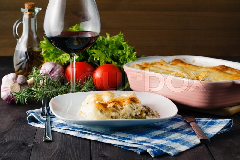 Stock image of 'mediterranean dinner with lasagne and glass of red wine'