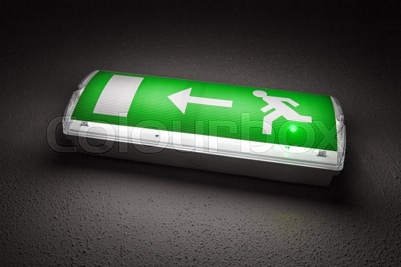 Stock image of 'Illuminated emergency exit sign mounted on the wall in dark room'
