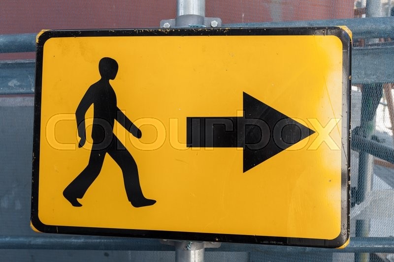 Stock image of 'Pedestrians bypass direction. Yellow road sign on construction site border'