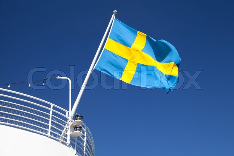 Stock image of 'Swedish flag mounted on the stern of white passenger ship waving over blue sky background'