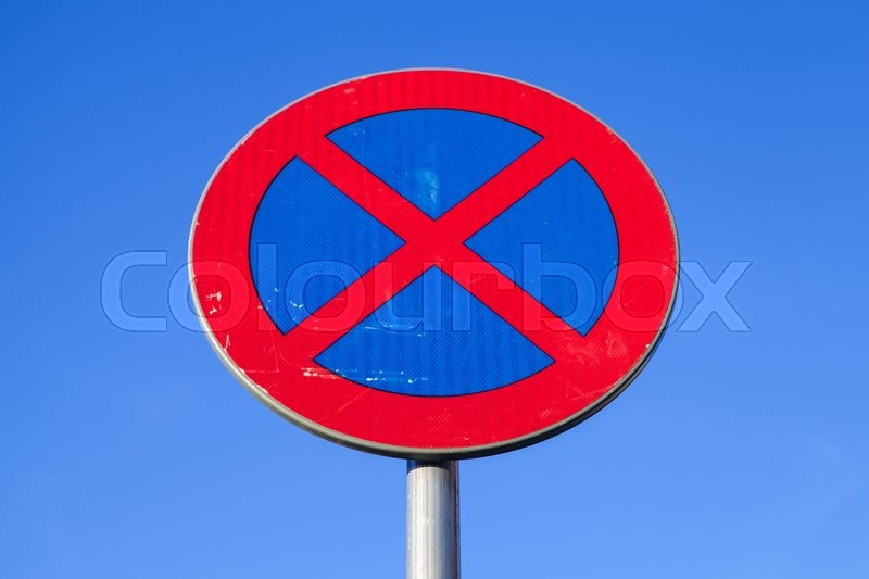 Stock image of 'Standing is prohibited. Round road sign over blue sky background'