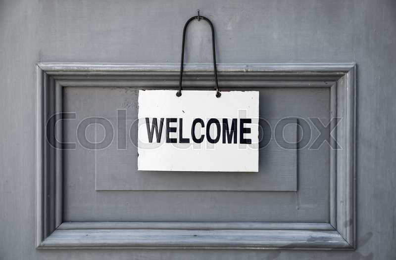Stock image of 'Welcome text plate hanging on gray wooden door'