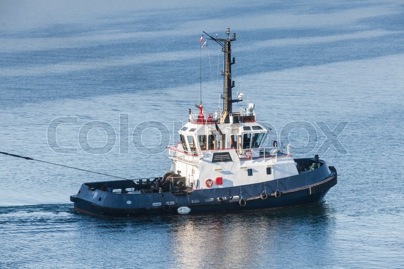 Stock image of 'Tug boat with white superstructure underway pulling the rope, side view'