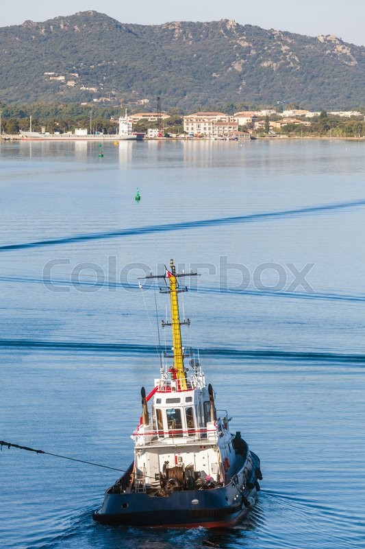 Stock image of 'Tug boat with white superstructure underway pulling the rope, vertical photo, rear view'