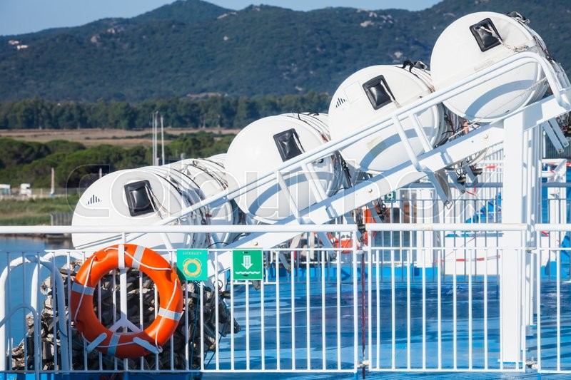 Stock image of 'Inflatable liferafts in hard-shelled white containers and red lifebuoy hanging on railings. Modern passenger ship safety equipment'