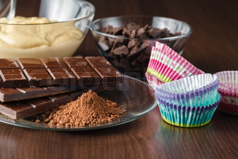 Stock image of 'Various muffins ingredients on dark wood table'