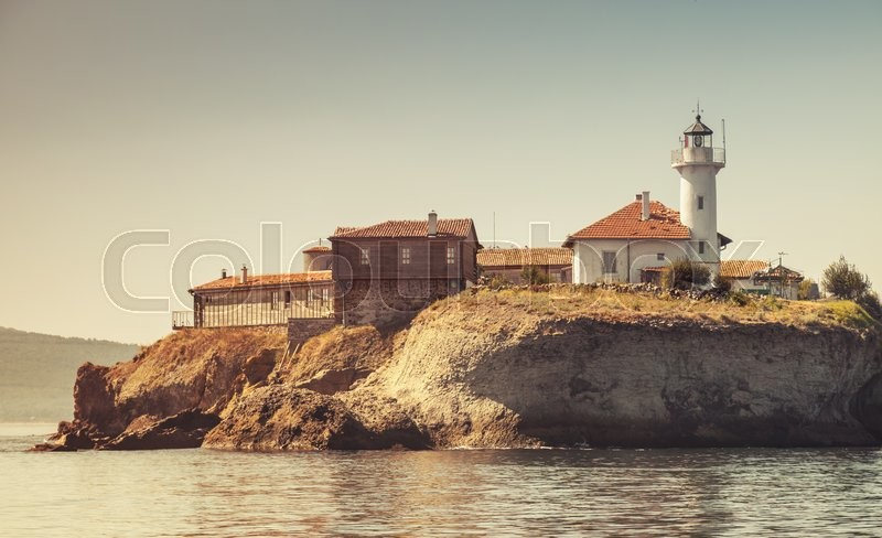 Stock image of 'Lighthouse and old wooden buildings on Saint Anastasia Island. Burgas bay, Black Sea, Bulgaria. Vintage tonal correction filter effect, stylized photo'