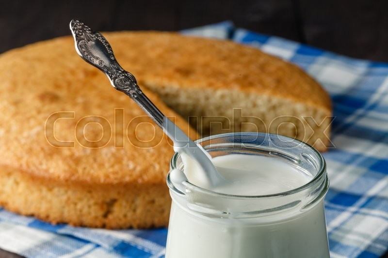 Stock image of 'Evening relax concept. Jar of yoghurt and pie on table'
