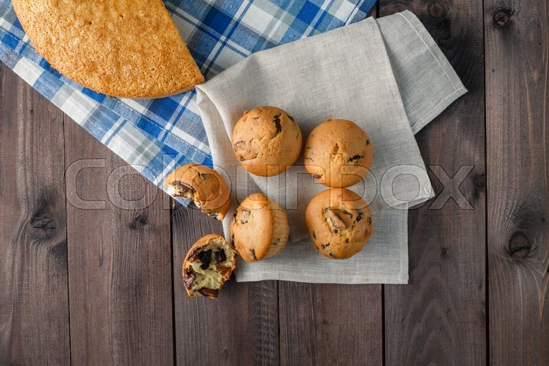 Stock image of 'Fresh backed muffins on wood table. Top view'