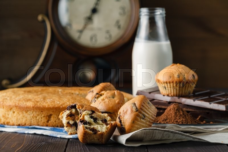 Stock image of 'Breakfast for energy day. Muffins and milk bottle on table'
