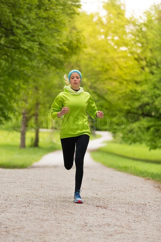 Stock image of 'Sporty young female runner in city park.  Running woman. Female runner during outdoor workout in nature. Fitness model outdoors. Weight Loss. Healthy lifestyle. '