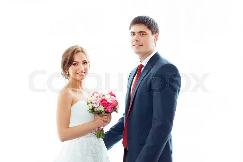 Stock image of 'Happy wedding couple in love. Beautiful bride in white dress with brides bouquet and handsome groom in blue suit standing looking to the camera indoors at home against big window, white bright background'