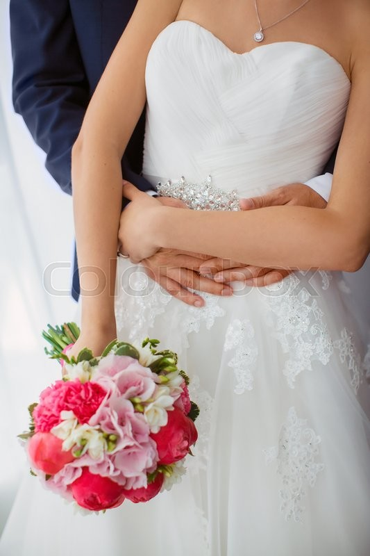 Stock image of 'Wedding couple details indoors. Beautiful bride in white dress and pink bridal bouquet of flowers and groom in blue suit close-up. No face, only body and hands.'