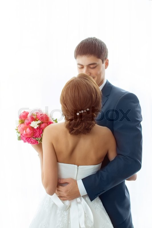 Stock image of 'Wedding couple in love. Beautiful bride in white dress with brides bouquet and handsome groom in blue suit standing and embracing each other indoors at home, white bright isolated background'