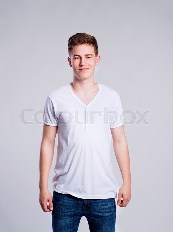 Stock image of 'Teenage boy in jeans and white t-shirt, young man, studio shot on gray background'