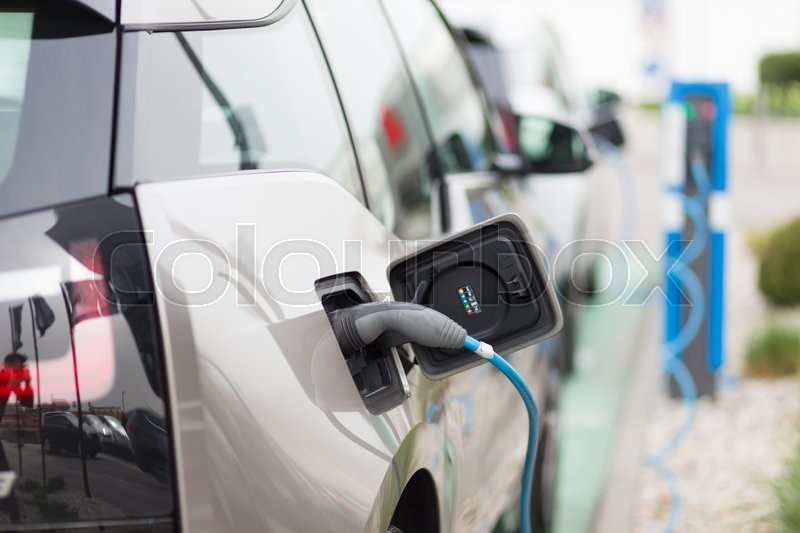 Stock image of 'Power supply for electric car charging.  Electric car charging station. Close up of the power supply plugged into an electric car being charged.'