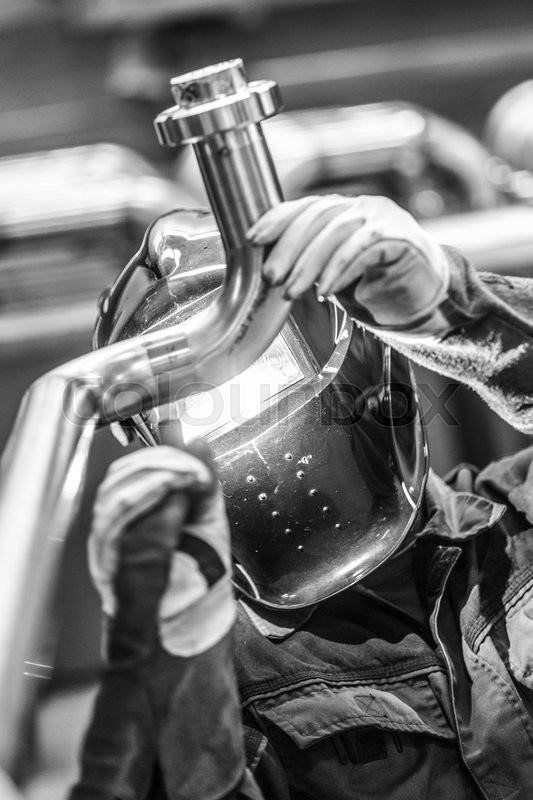 Stock image of 'Industrial worker with protective mask welding inox elements in steel structures manufacture workshop. Black and white photo.'