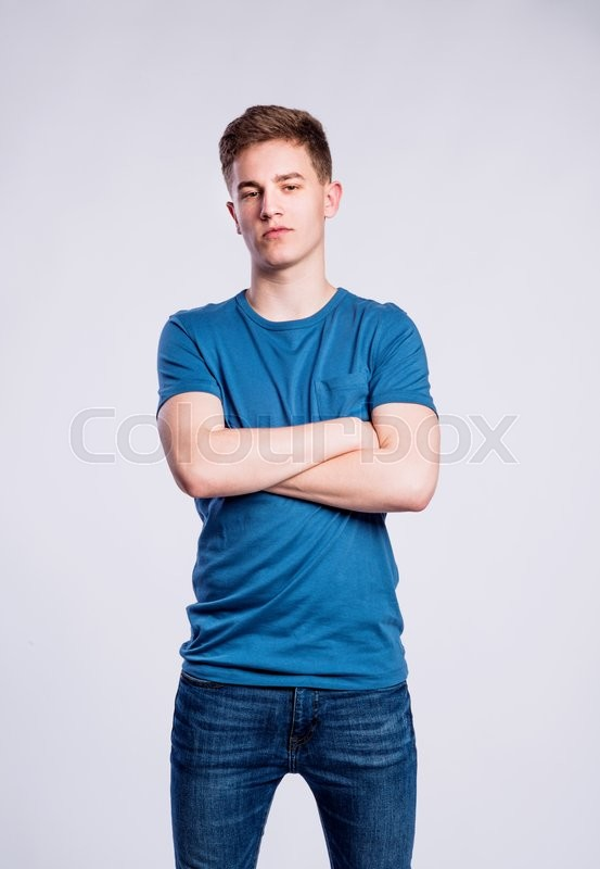 Stock image of 'Teenage boy in jeans and blue t-shirt, young man, studio shot on gray background'